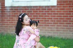 Fostra kramar hennes litet behandla som ett barn flickan på gräsmattan Arkivfoton