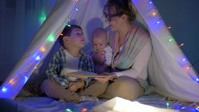 Fostra med behandla som ett barn på händer berättar sonen en saga i vigvammet inom deras hus i afton arkivfilmer