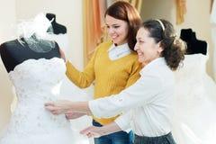 Fostra med dottern väljer den brud- kappan Arkivbilder