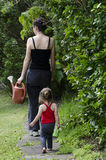 Fostra och att arbeta i trädgården för dotter royaltyfri fotografi