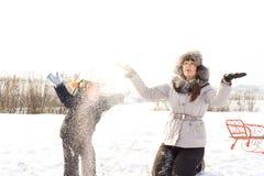 Fostra och barnet som leker i snowen Arkivbilder
