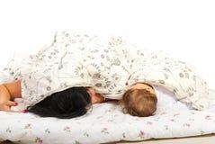 Fostra och behandla som ett barn att sova i säng Royaltyfria Bilder