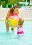 Fostra och behandla som ett barn att spela med bollen i simbassäng Arkivbilder