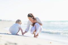 Fostra och behandla som ett barn att spela på stranden arkivbild