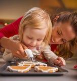 Fostra och behandla som ett barn dekorera hemlagade julkakor med glasyr Arkivfoto