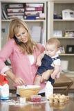 Fostra och behandla som ett barn dottern som förbereder ingredienser för att baka kakor i kök Arkivfoton