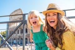 Fostra och behandla som ett barn flickan framme av colosseumen i rome Arkivbilder