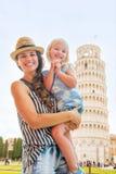Fostra och behandla som ett barn flickan framme av tornet av pisa Arkivbild