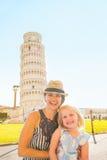 Fostra och behandla som ett barn flickan framme av tornet av pisa Fotografering för Bildbyråer