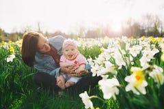 Fostra och behandla som ett barn flickan i vår parkerar bland blomningfält fotografering för bildbyråer