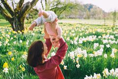 Fostra och behandla som ett barn flickan i vår parkerar bland blomningfält royaltyfri bild