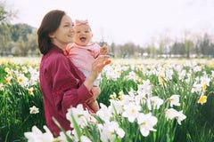 Fostra och behandla som ett barn flickan i vår parkerar bland blomningfält royaltyfria bilder