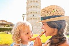 Fostra och behandla som ett barn flickan som äter pizza i pisa Royaltyfri Fotografi