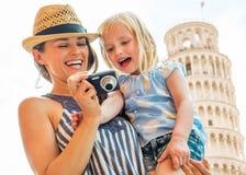 Fostra och behandla som ett barn flickan som in camera kontrollerar foto Royaltyfri Fotografi