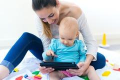 Fostra och behandla som ett barn flickan som hemma använder den digitala minnestavlan Arkivbilder