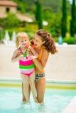 Fostra och behandla som ett barn flickan som spelar i simbassäng Royaltyfri Fotografi