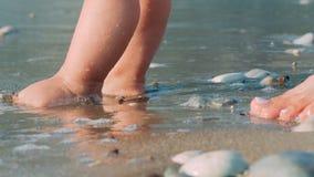 Fostra och behandla som ett barn fot som går på sandstranden Nyfödd ungefot på stranden arkivfilmer