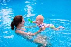 Fostra och behandla som ett barn i en simbassäng royaltyfri fotografi