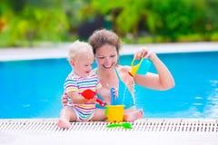 Fostra och behandla som ett barn i simbassäng Fotografering för Bildbyråer