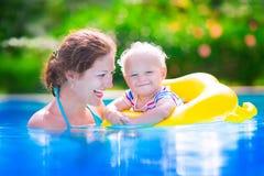 Fostra och behandla som ett barn i simbassäng Arkivbild