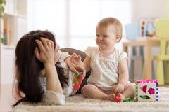 Fostra och behandla som ett barn lek med leksaker i barnkammare royaltyfri foto