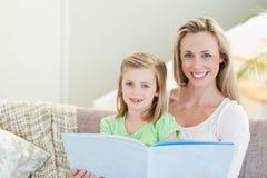 Fostra och dotterläsning en tidskrift på sofaen Arkivfoton