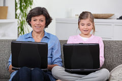 Fostra och dottern med datorer Fotografering för Bildbyråer
