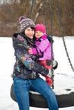 Fostra och dottern på vinterseesawen Arkivfoton