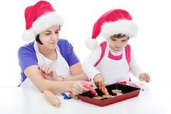 Fostra och dottern som förbereder kakor Arkivbild