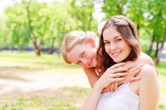 Fostra och dottersammanträde tillsammans på gräset arkivfoto