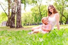 Fostra och dottersammanträde tillsammans på gräset royaltyfri foto