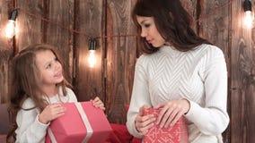 Fostra och en gullig liten flicka som rymmer Xmas-gåvor och försöker att gissa vilken ` s inom arkivfoton