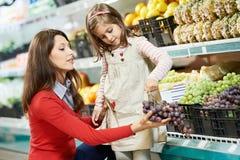 Fostra och flickashopping i supermarket Royaltyfria Bilder