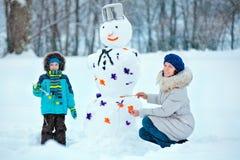 Fostra och henne lite sonen som målar en snowman royaltyfri fotografi