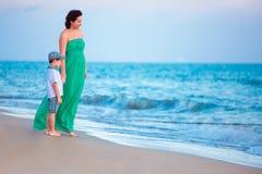 Fostra och henne lite sonen som tycker om stranden royaltyfri foto
