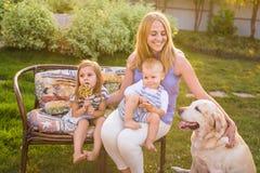 Fostra och hennes barn som kopplar av i trädgård med den älsklings- hunden Lycklig familj som spelar med deras labrador retriever royaltyfri fotografi