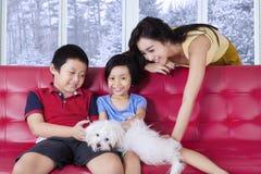 Fostra och hennes barn som spelar hunden på soffan Arkivbilder