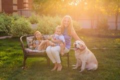 Fostra och hennes dotter och son i trädgården med en golden retrieverhund arkivbilder