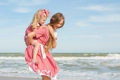 Fostra och hennes dotter som har gyckel på stranden Royaltyfri Foto