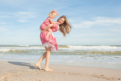 Fostra och hennes dotter som har gyckel på stranden Royaltyfri Fotografi