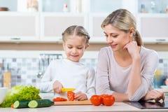Fostra och hennes dottermatlagning i köket Arkivbild