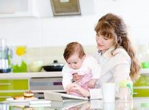 Fostra och hennes lilla dotter med minnestavlaPC Royaltyfri Foto