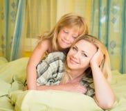Fostra och hennes lilla dotter som ligger, i säng och att le familj Sängtid Fotografering för Bildbyråer