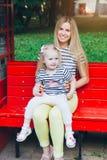 Fostra och hennes lilla dotter som vilar på en bänk royaltyfri bild
