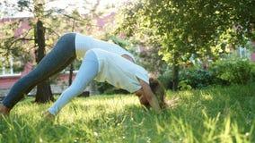 Fostra och hennes lilla gulliga dotter som tillsammans gör yogaövning arkivfilmer