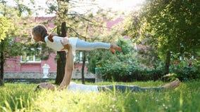 Fostra och hennes lilla gulliga dotter som tillsammans gör yogaövning lager videofilmer