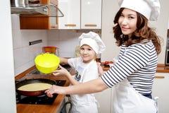 Fostra och hennes son i vita kockhattar som förbereder en omelett i köket Arkivfoton