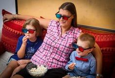 fostra och hennes son med exponeringsglas som 3d ser en film Arkivbild