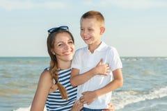 Fostra och hennes son som har gyckel på stranden Royaltyfri Bild