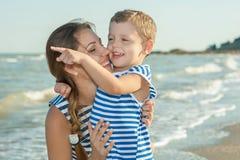 Fostra och hennes son som har gyckel på stranden Arkivbild